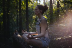 Woman meditating in nature; this is one way to practice calm parenting